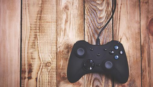 https://tickertapecdn.tdameritrade.com/assets/images/pages/md/Video game controller on top of wood boards