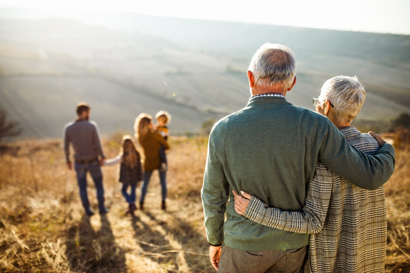https://tickertapecdn.tdameritrade.com/assets/images/pages/md/Elderly couple with arms around each other gazing at their family: Estate planning basics