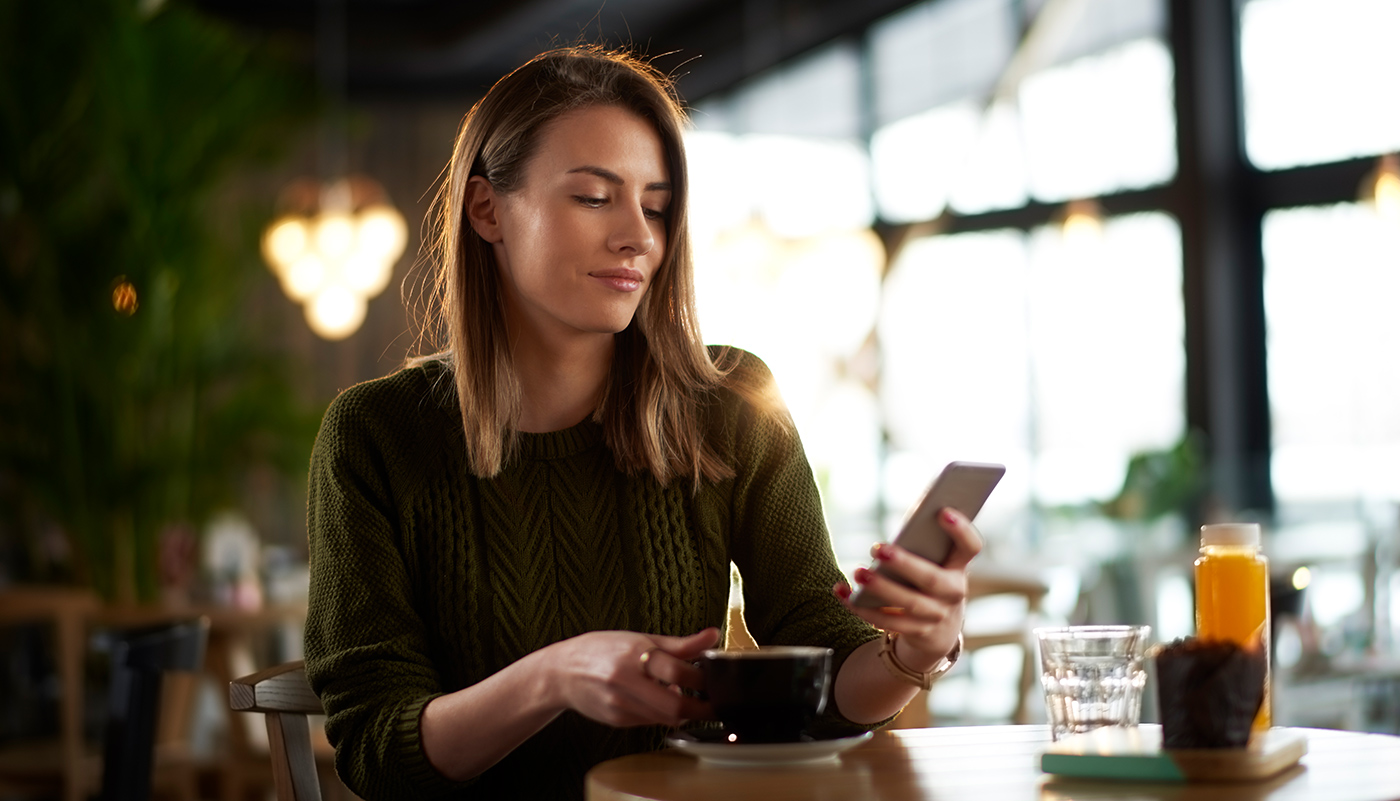 https://tickertapecdn.tdameritrade.com/assets/images/pages/md/Woman checking social media on her smartphone