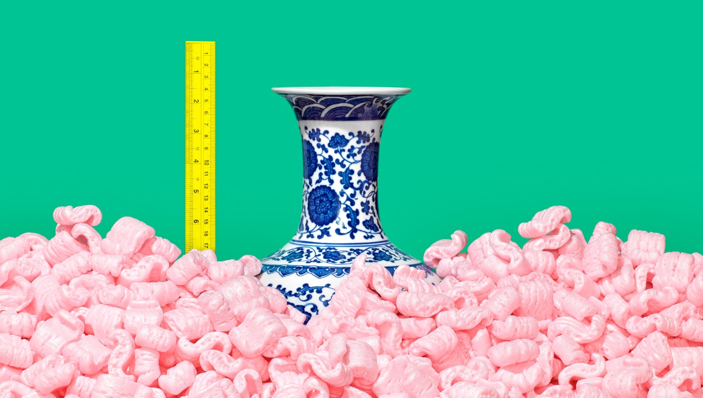 https://tickertapecdn.tdameritrade.com/assets/images/pages/md/Classic blue and white fine china vase half buried in pink Styrofoam peanuts with ruler to measure height of vase
