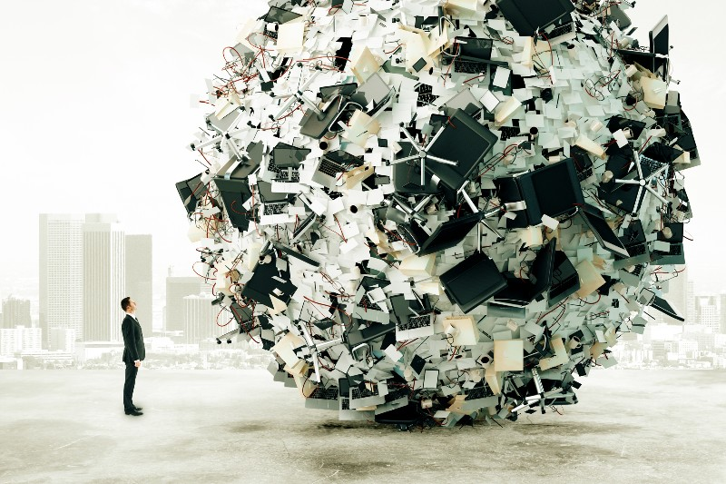 Businessman looking up at giant ball of office furniture and supplies: Targeting conglomerate stocks